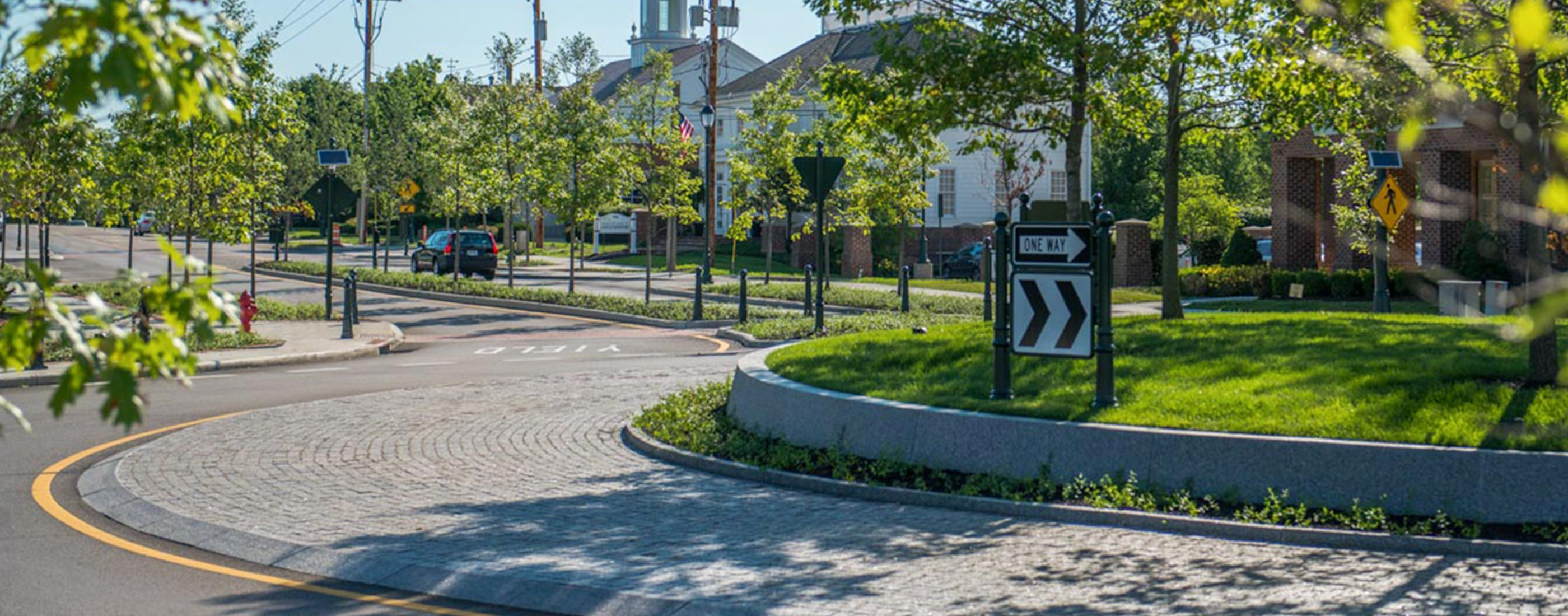 The center of New Albany, Ohio central roundabout, designed by OHM Advisors, is anchored by trees and a low granite wall.