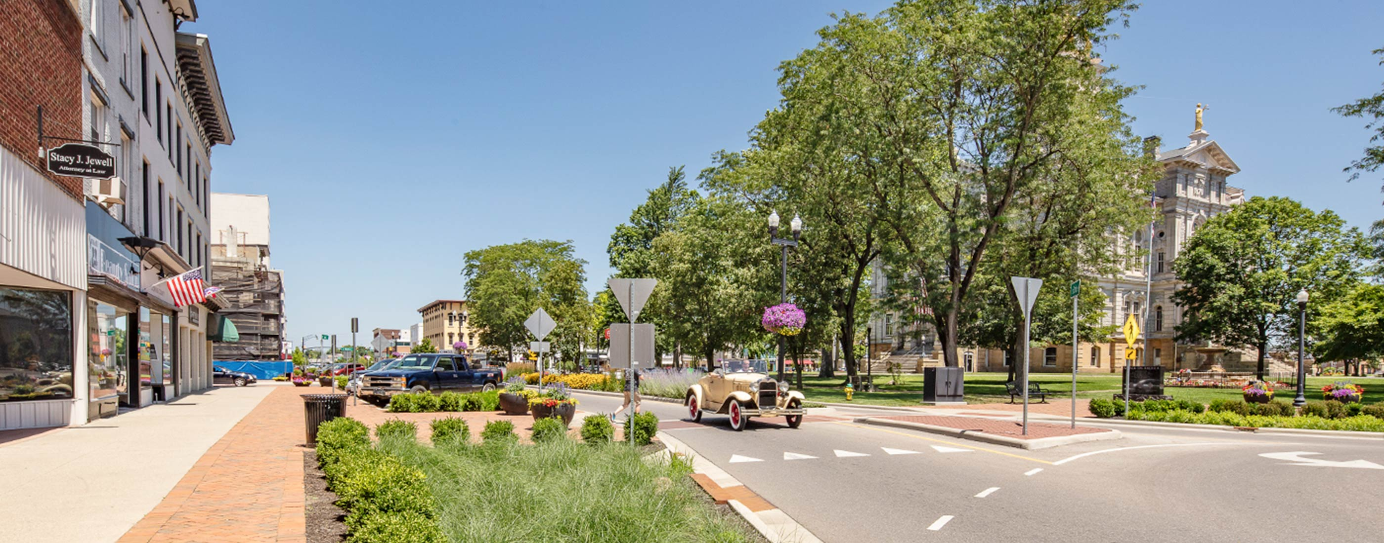 An old car drives through Newark, Ohio's roundabout and streetscape.
