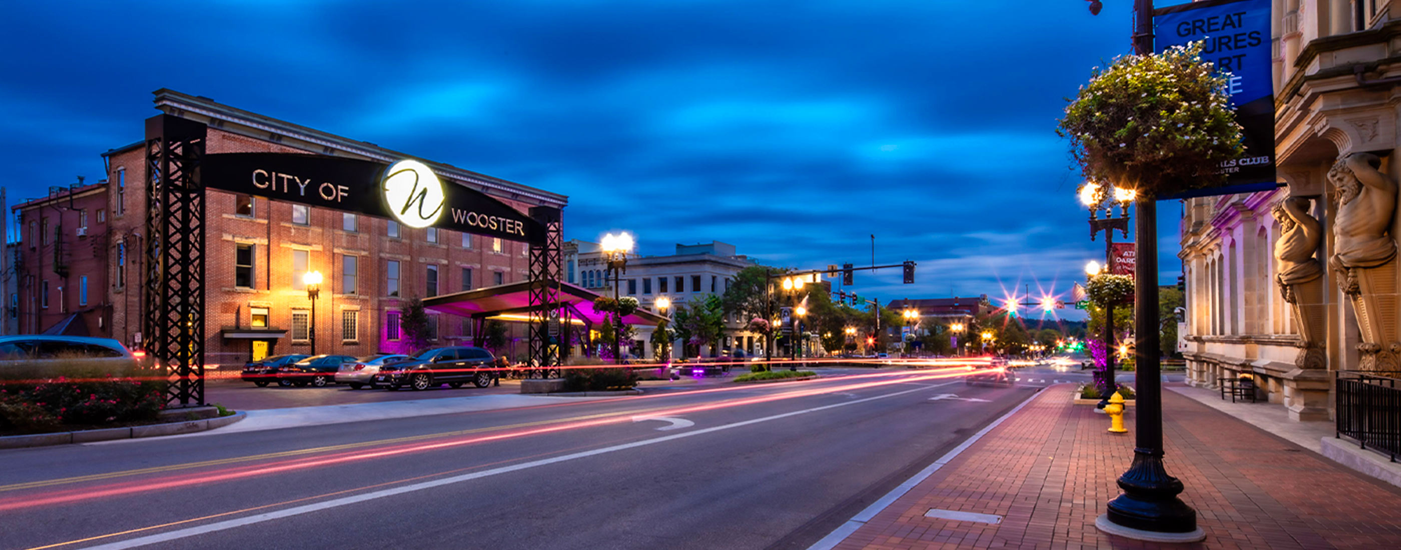 Cars drive through Downtown Wooster, Ohio streetscape at night.