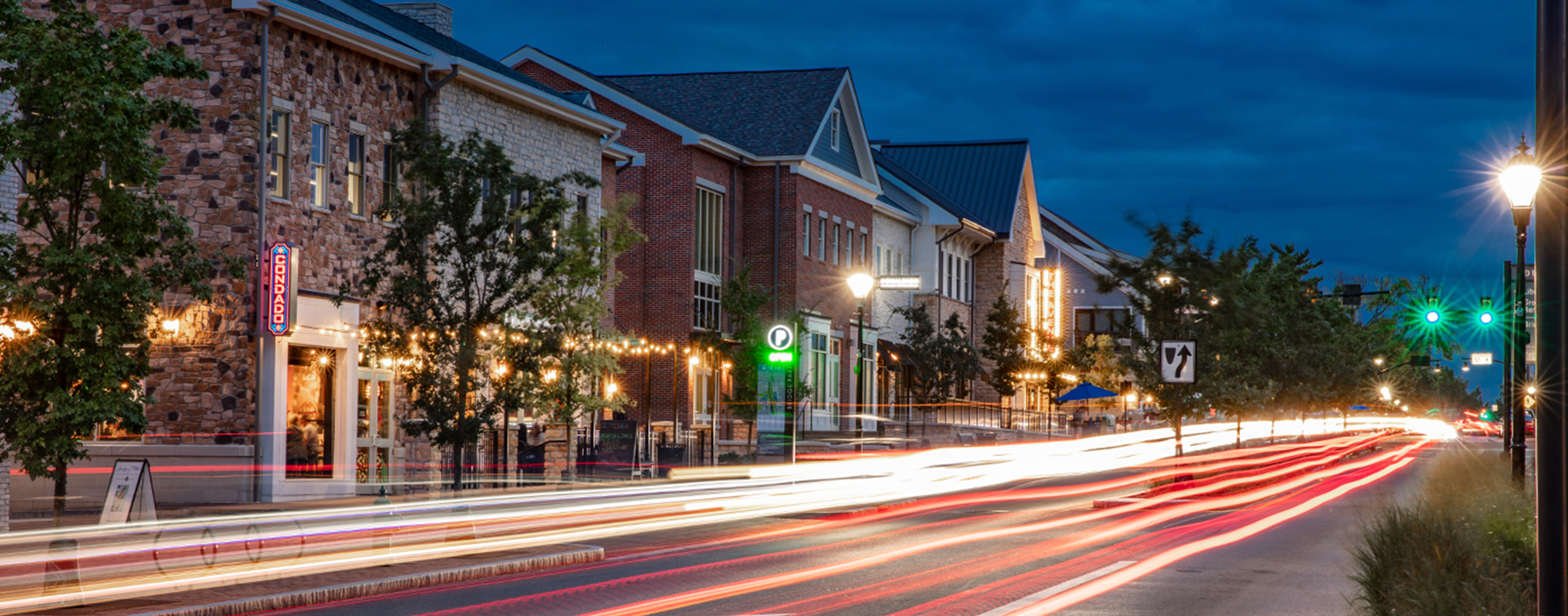 The City of Dublin, Ohio's Bridge Park West streetscape lit up at night.