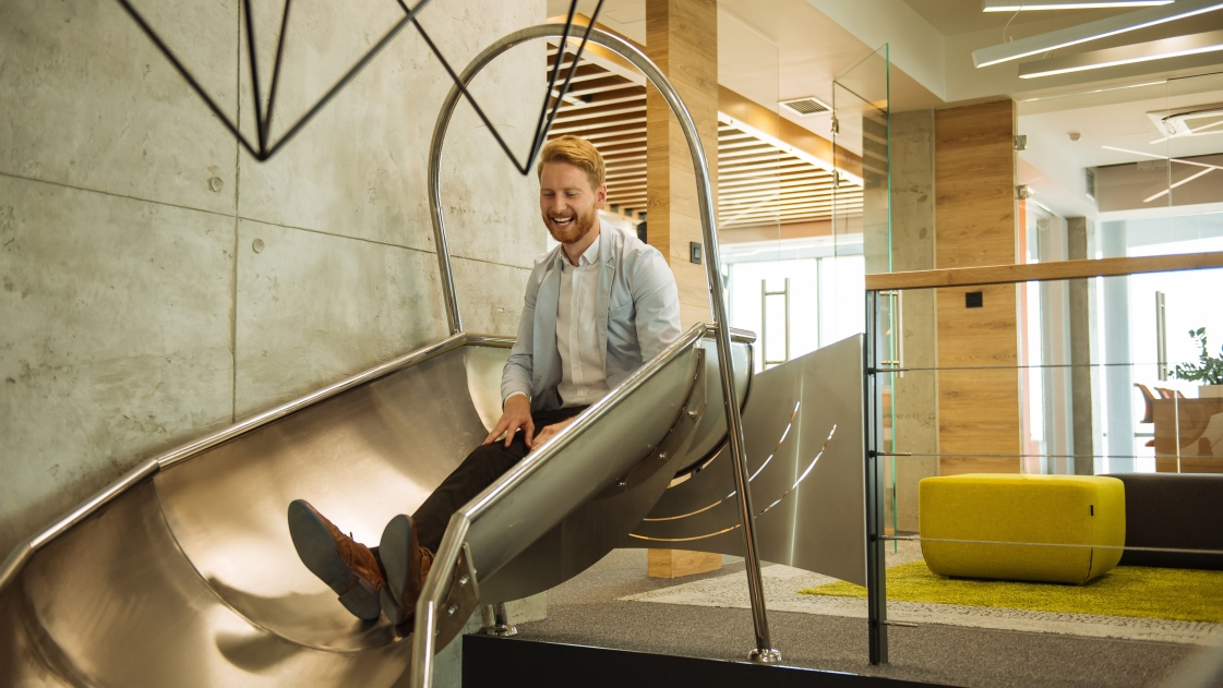 Man sits on slide in office place