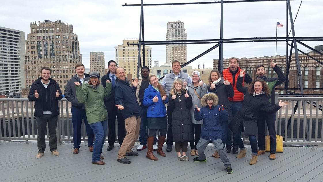 A group of OHM Advisors employees pose on a Detroit roof.