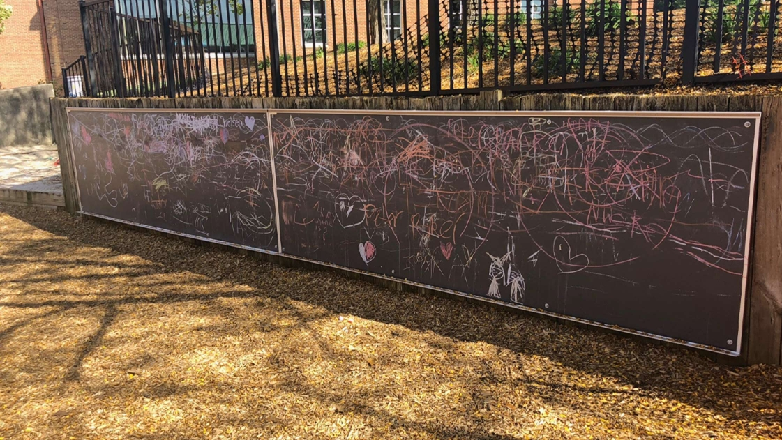 Chalkboards line this border wall to encourage creativity.
