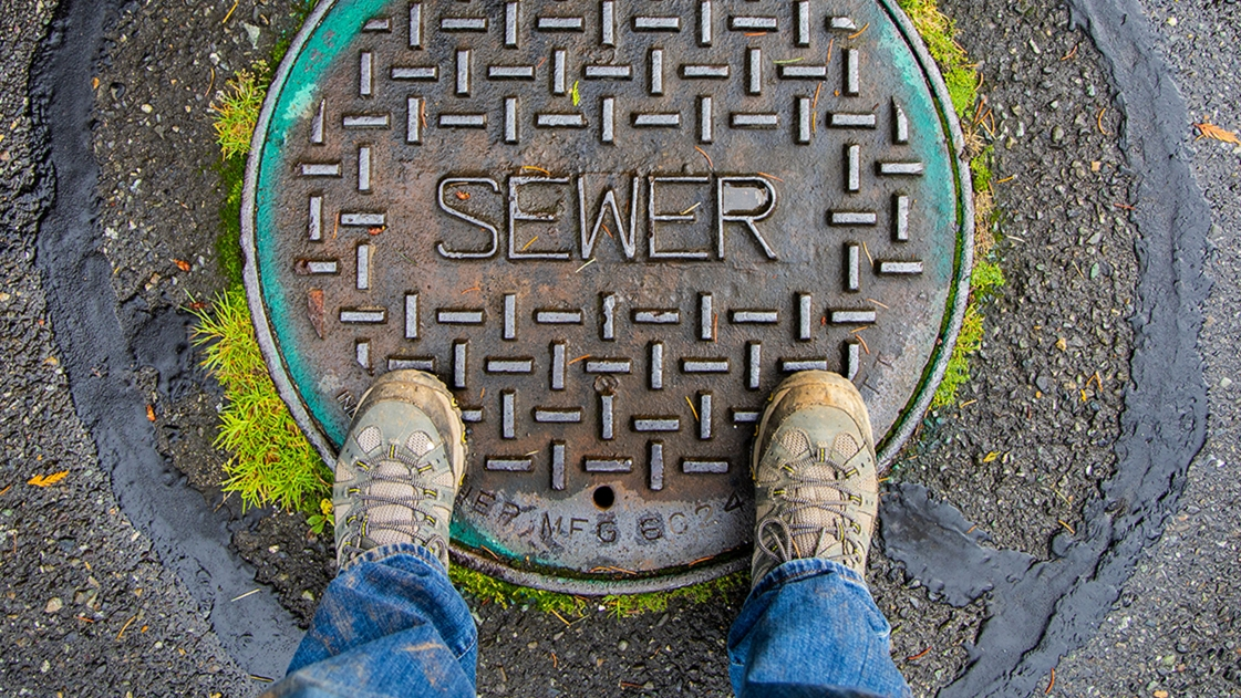 A asset management expert stands over a sanitary sewer cap.