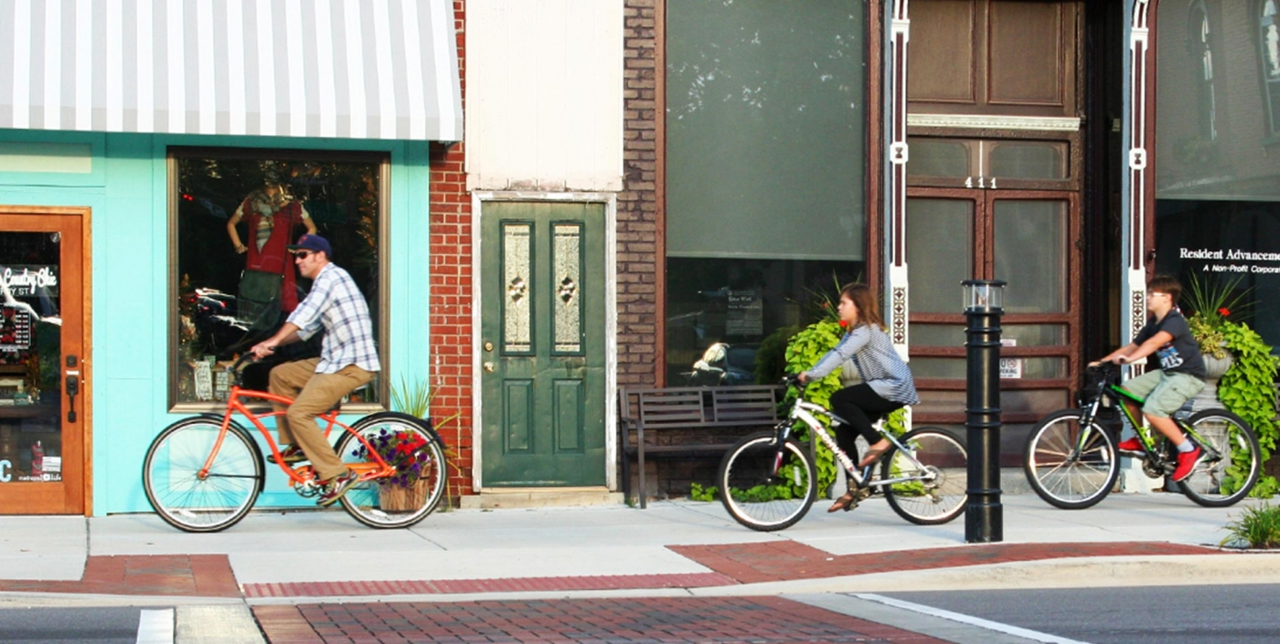 A family enjoys a bike ride along Fenton, Michigan's new downtown streetscape, a project led by OHM Advisors.