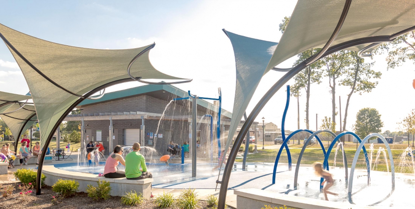Children play at splash park, while parents watch from under the cover of shade structures.