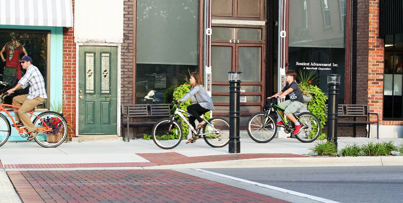 Bicyclists riding on the sidewalk in downtown Fenton.