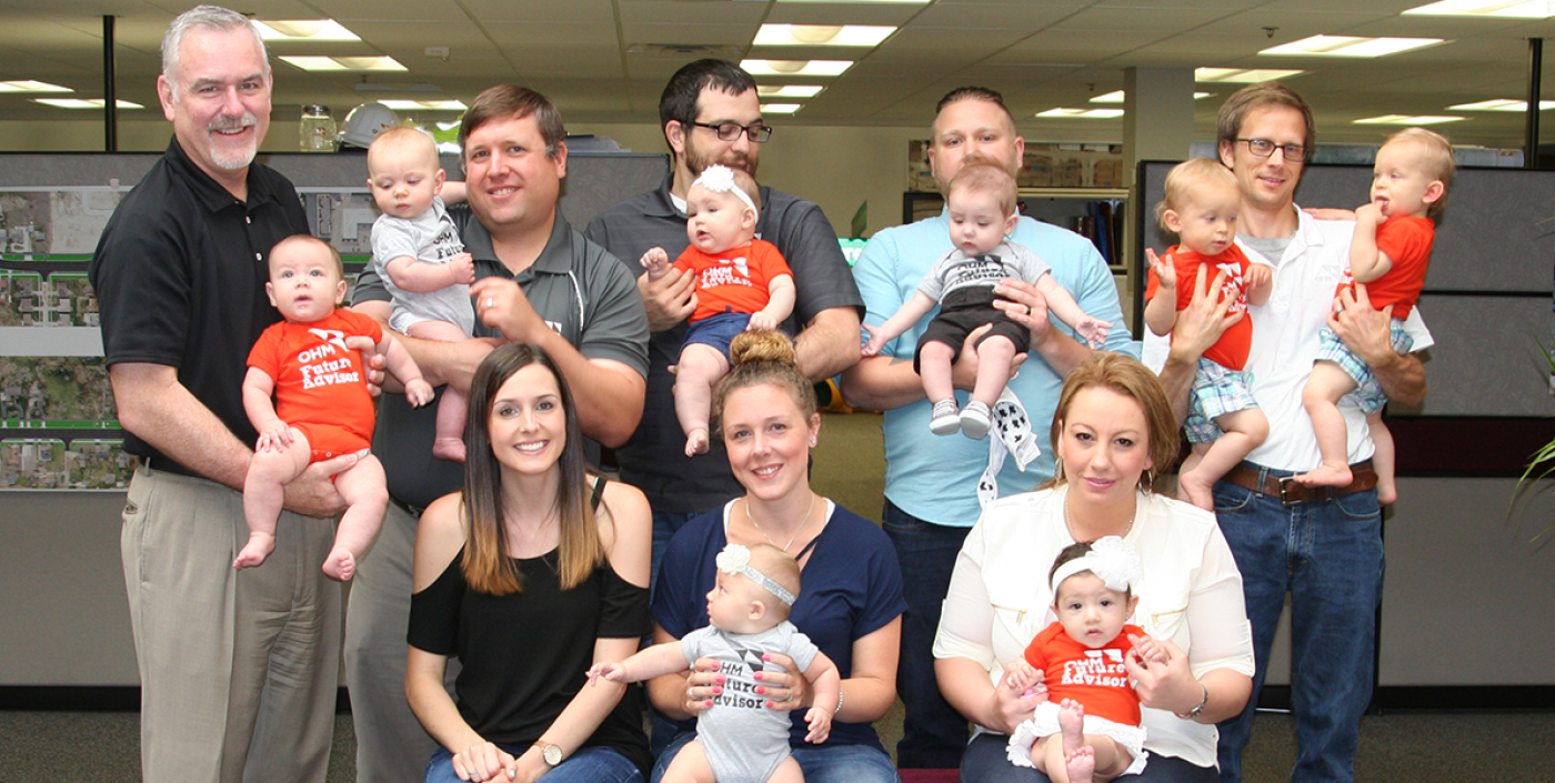 OHM Advisors' staff with their newborn babies, who show their flare in extra small OHM Advisors logo wear.