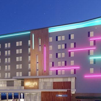 The proposed Aloft Hotel lit up at night.