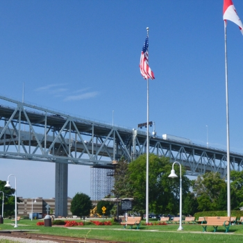 Canadian and American flags wave near the Blue Water Bridge.