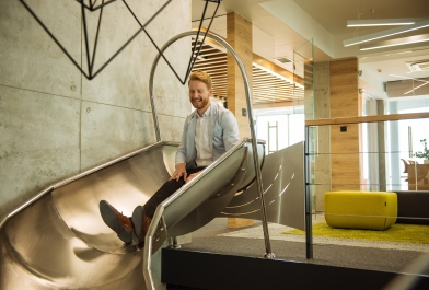 Man sits on slide in office workplace