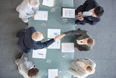 Men and women shake hands in a boardroom
