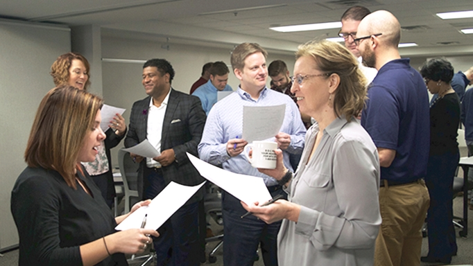 Professionals stand and talk at a diversity and inclusion training event.