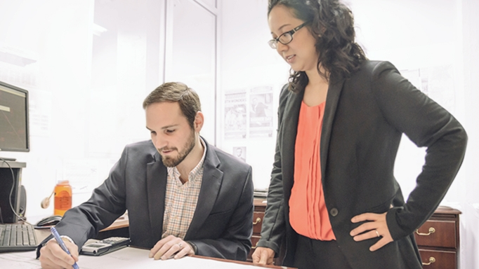 Two young professionals work together on a project at OHM Advisors.