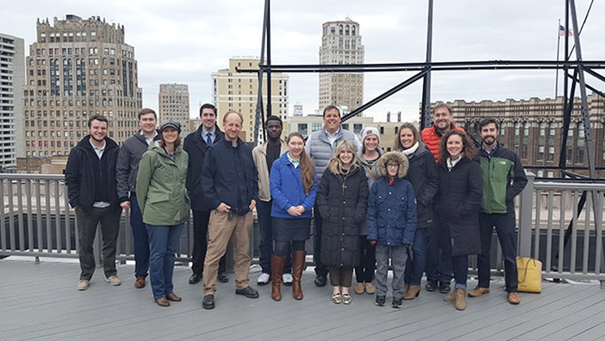 OHM Advisors' Detroit office staff on the roof of their building with downtown skyline in background