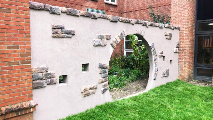 A rock wall invites children into a learning garden.